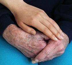 Young put her hand on senior lady's hands