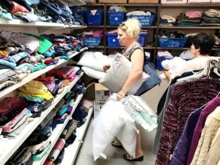 Woman picking out clothing and holding bags of household items in Israel Relief Aid Center