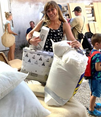 Mother holding her household items in Israel Relief Aid Center