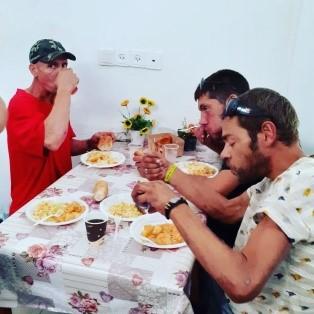 Men eating a meal at the Tel Aviv Homeless Center
