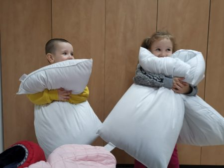 Children hugging their new pillows at Ariel Aid Center