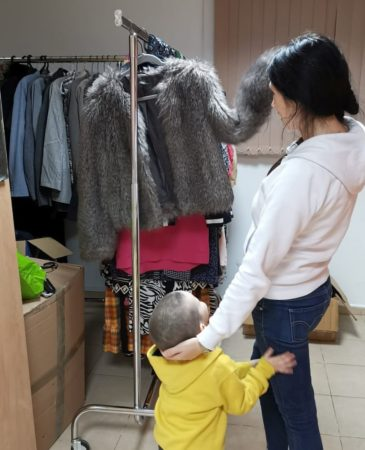 Mother with child picks out clothing at Ariel Aid Center
