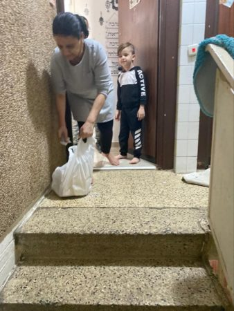 Mother and child receiving Israel Relief Aid grocery bag