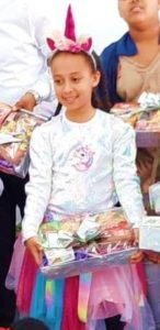 Ethiopian child in Haifa with Purim gift box from Israel Relief Aid