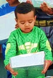 Ethiopian Israeli boy holding Purim gift box from Israel Relief Aid