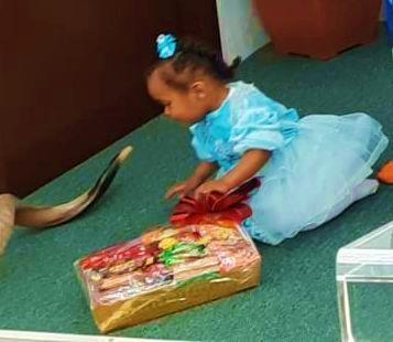 Ethiopian Israeli girl holding Purim gift box from Israel Relief Aid