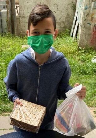 Boy receiving Passover Food Bags for families in Bat Yam