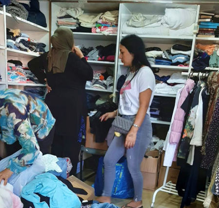 Women browsing through clothing at Haifa Aid Center