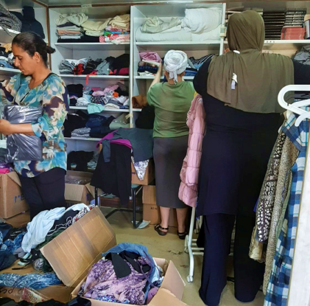 Israeli women in need browsing clothing at Haifa Aid Center