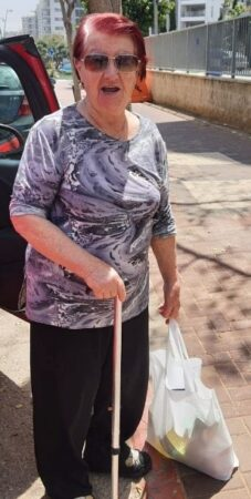 Holocaust Survivor in Israel receiving grocery bags from Israel Relief Aid for Yom HaShoah